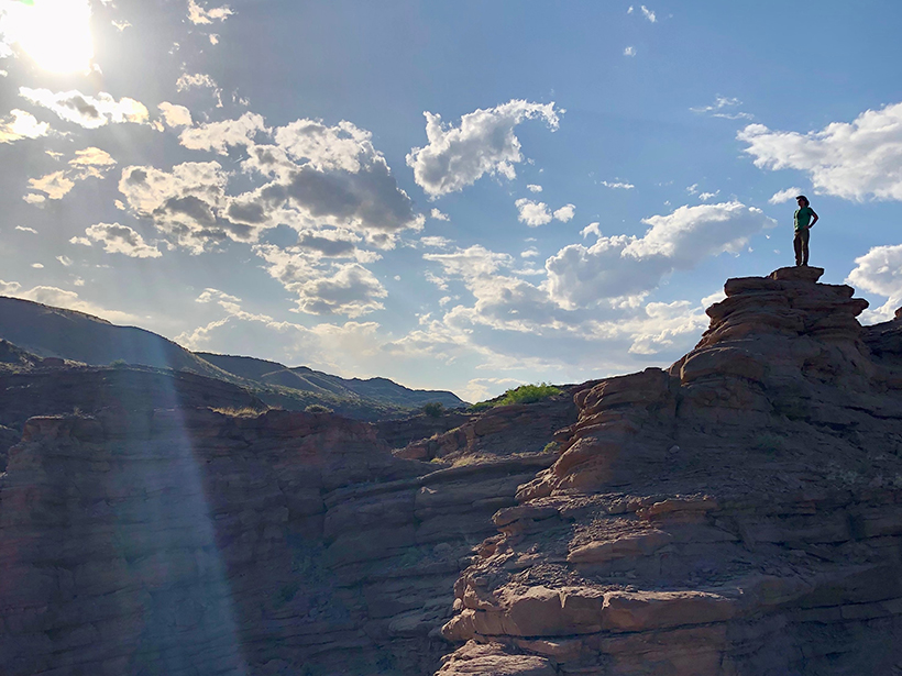 A person stands on the rim of a canyon in New Mexico with the Sun shining down