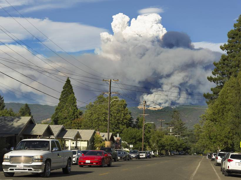 Smoke billows in the distance from a mountain near Ukiah, Calif., as motorists drive down a street in the foreground.