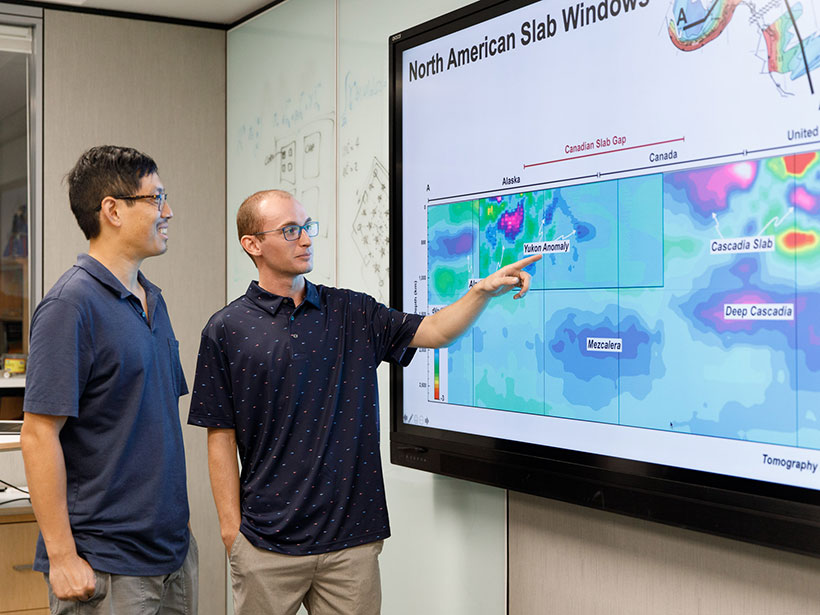 Jonny Wu (left) and Spencer Fuston point to a slide displaying mantle tomography in the North Pacific Ocean.