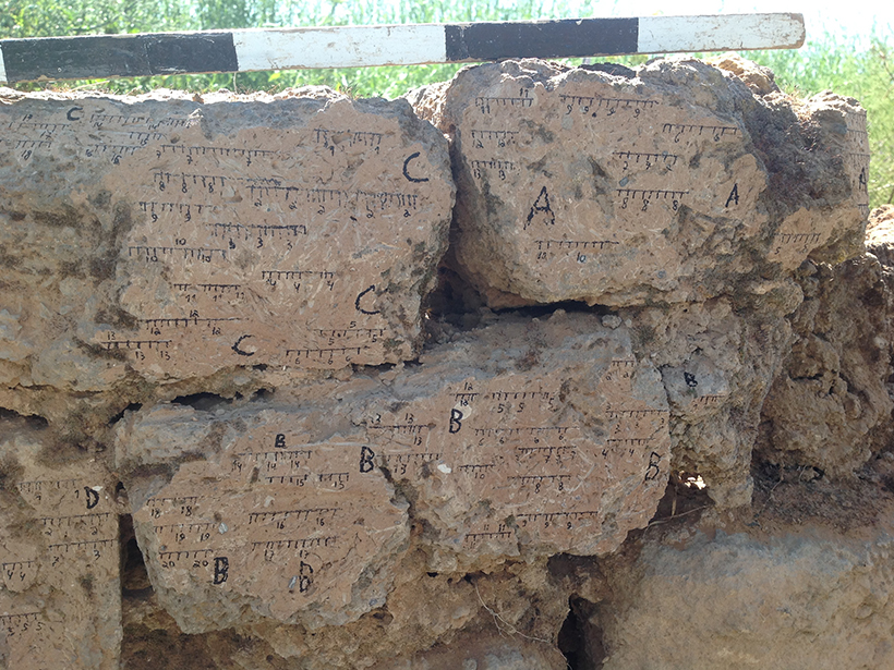 A mud brick wall marked with labels and measurements
