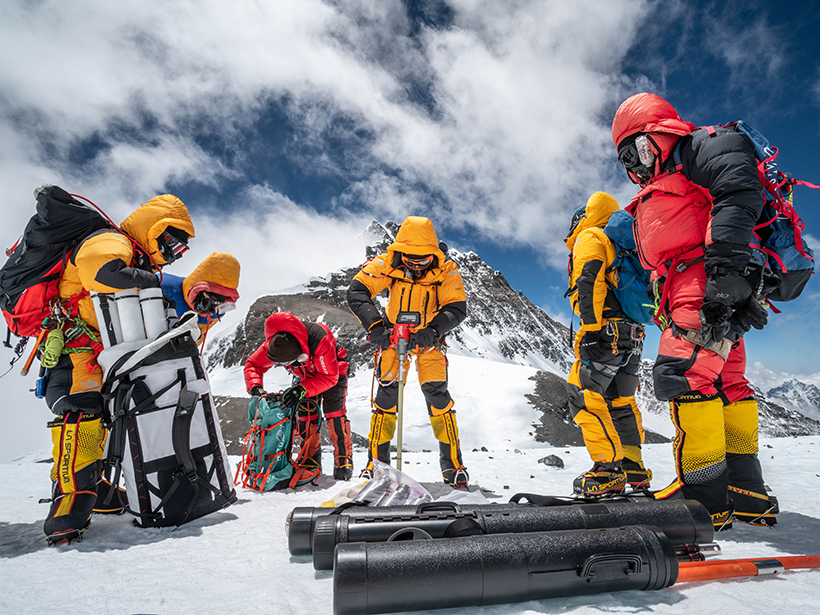 Six people in bright snowsuits and goggles drill an ice core on Mount Everest with mountains and clouds in the background.
