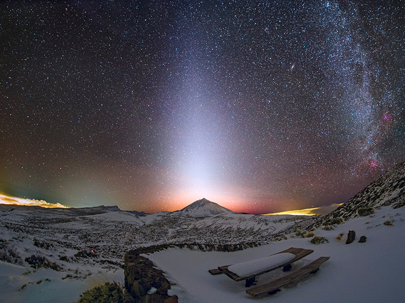 A column of zodiacal light stretches skyward in the star-filled night sky beyond Mount Teide in the Canary Islands.