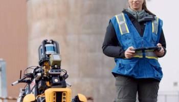 A woman operates a four-legged robot