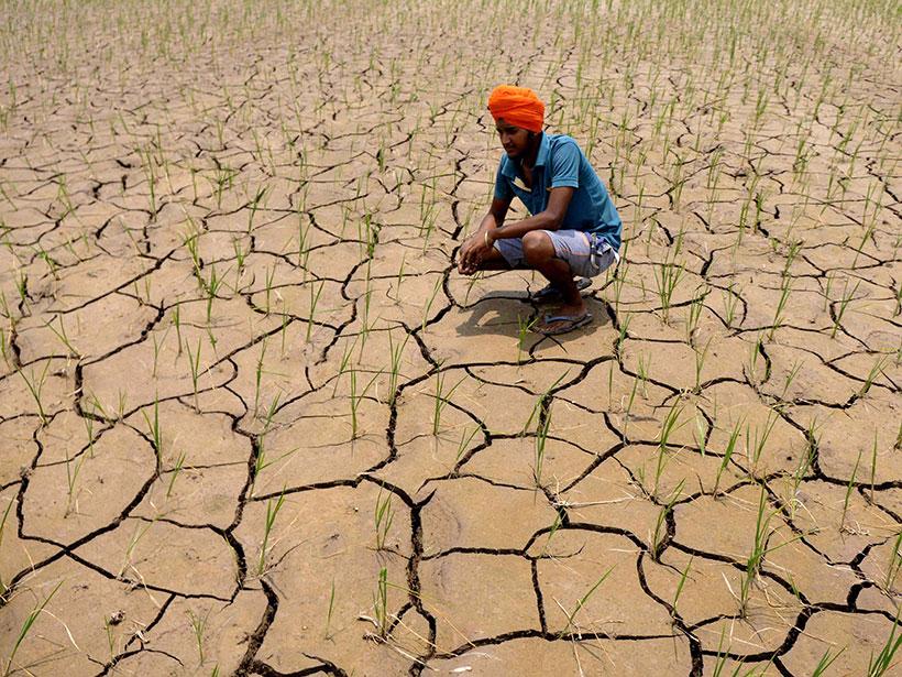 Un agricultor se agacha sobre suelo seco y agrietado en su granja en Punjab.