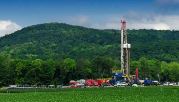 A large gas well sits in Pennsylvania fields and foothills.