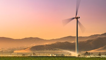 A wind turbine towers over an irrigated farm field with mountains in the distance