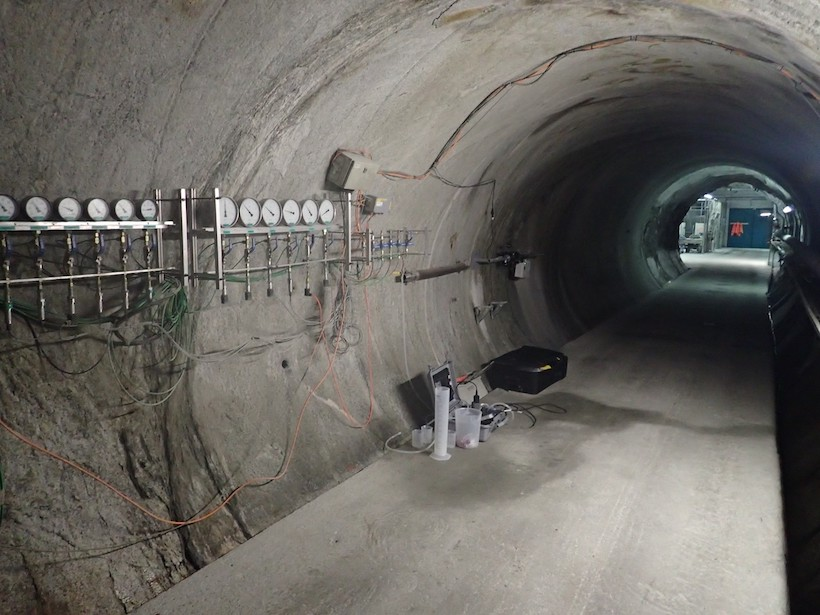 View looking down an underground tunnel with various gauges and water sampling equipment visible
