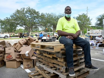 Mario Wilcox takes a break after volunteering at a community food giveaway in Fort Pierce, Fla.