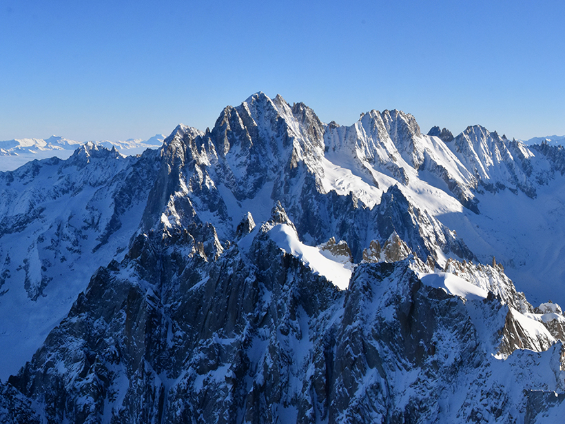 Steep, snow-covered mountains extend to the horizon.