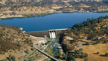 A blue reservoir lake surrounded by yellow hills with spotty dark green tree coverage flows into a hydroelectric dam.