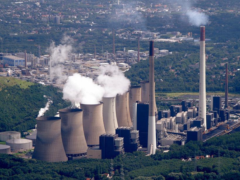 Imagen de una fábrica en un complejo industrial emitiendo gases.