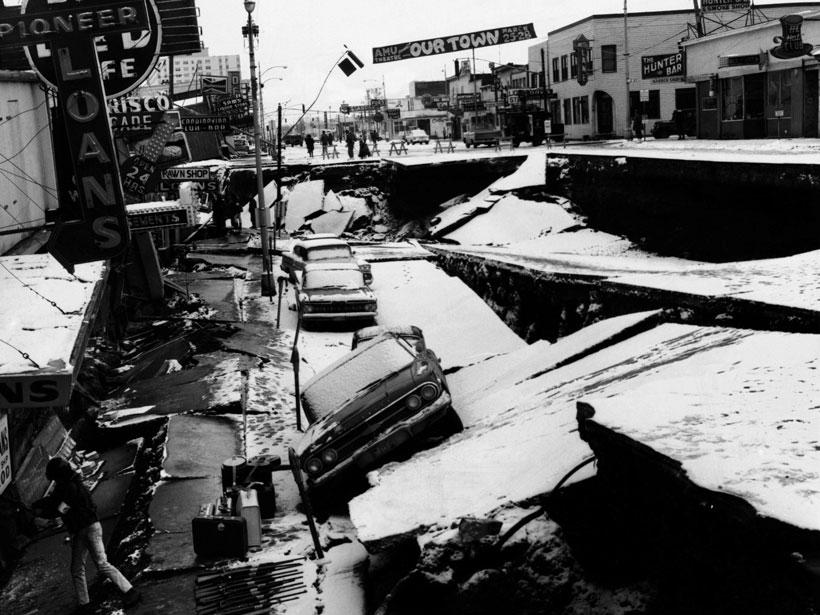 Black and white photo showing a damaged road and storefronts in Anchorage, Alaska, following the March 1964 earthquake