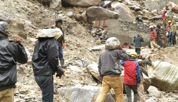 Workers clear flood and landslide debris from a cliffside