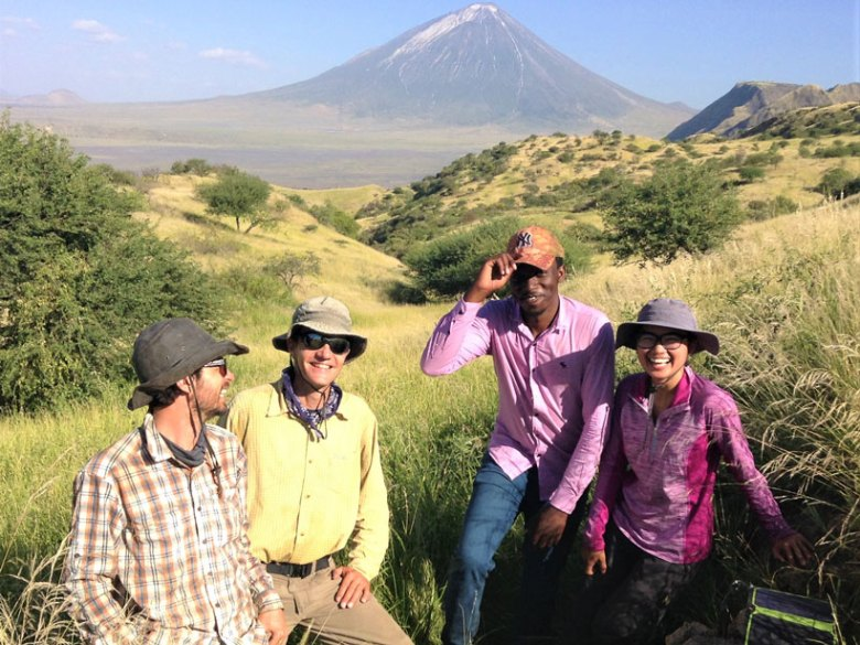 Researchers pose for a photo while standing in tall grass with a volcano rising in the background behind them