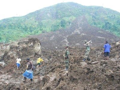 Civilians and soldiers walk through debris from a huge landslide in Uganda.