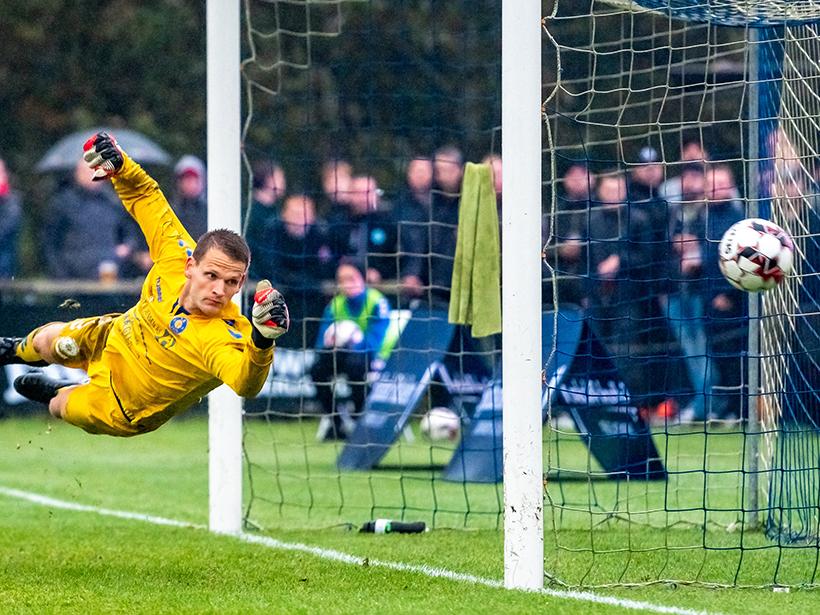 A soccer goalie dives for the ball