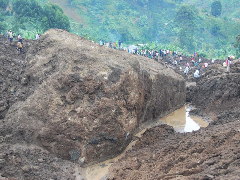 People stand atop debris from a huge slump landslide in Uganda.