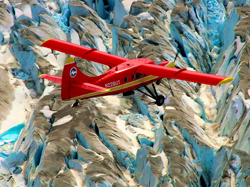 A photograph of a plane flying over mountain glaciers in Alaska