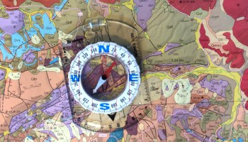 Traditional low-tech compass on a geologic map