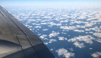 View out the window of an airplane with part of a wing and cumulus clouds below visible