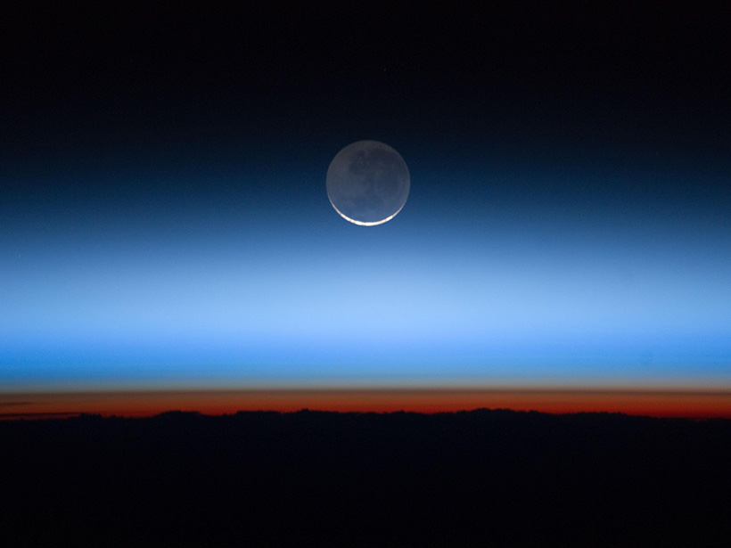 The moon appears at the top of the layers of atmosphere above the dark Earth. The orange-red glow is Earth's troposphere, and the brown transitional layer is the tropopause.