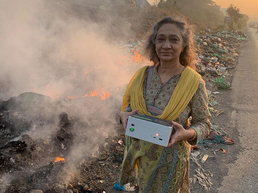 Environmental activist Sumaira Abdulali measures particulate matter emitted by a burning roadside garbage dump near Mumbai, India.