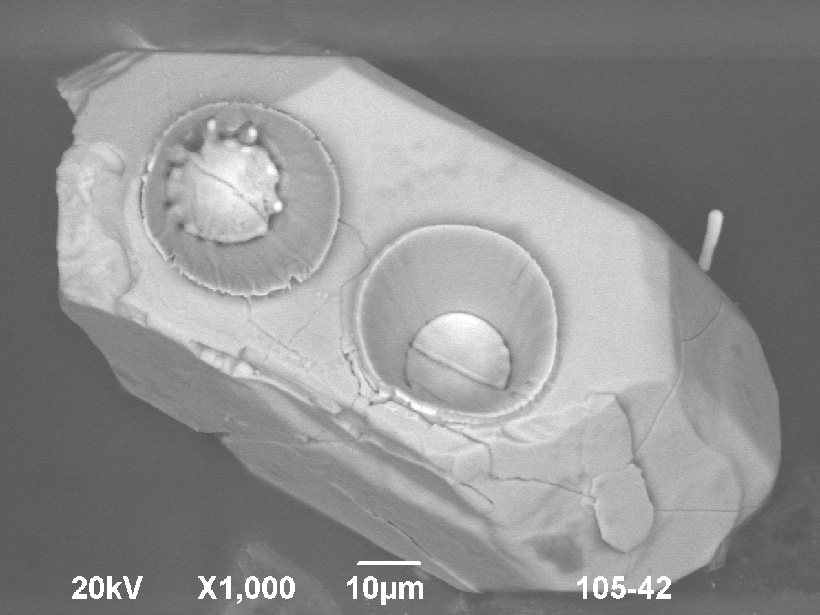 Grayscale scanning electron microscope image of an unpolished tetrahedral zircon crystal with two laser ablation pits, each between 25 and 30 micrometers in diameter