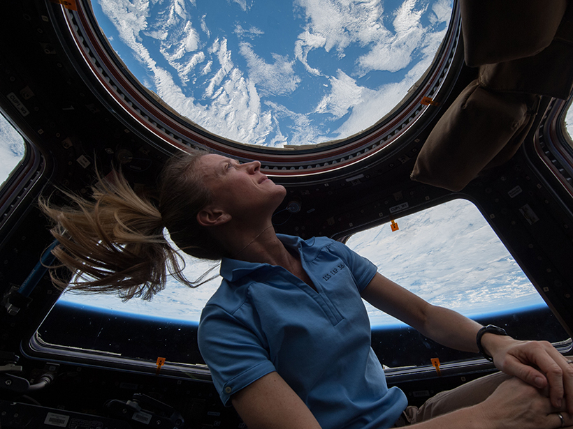 NASA astronaut Karen Nyberg enjoys a view of Earth from the windows of the International Space Station. Earth looks blue and white, with a thin layer of atmosphere at its limb.