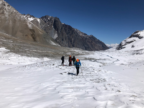 Four people stand on snowy ground in a high mountain valley.