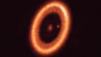 A bright orange ring of dust surrounds a fuzzy orange center that hides the central star of the PDS 70 system. Sitting between the central star and the planet-forming dust disk is a small, bright orange dot that is the young planet PDS 70 c.