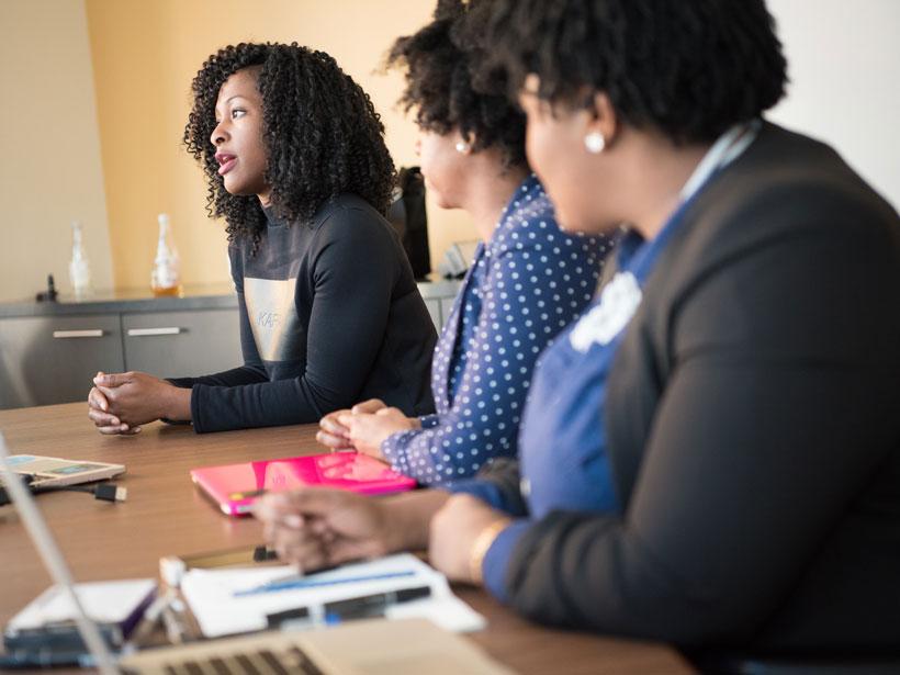 Mujeres trabajando en laptops en una junta de negocios.