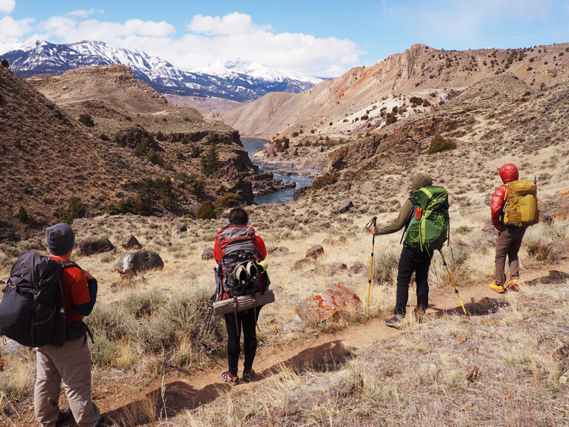 Four backpackers look down the Yellowstone River where it flows through the Black Canyon.