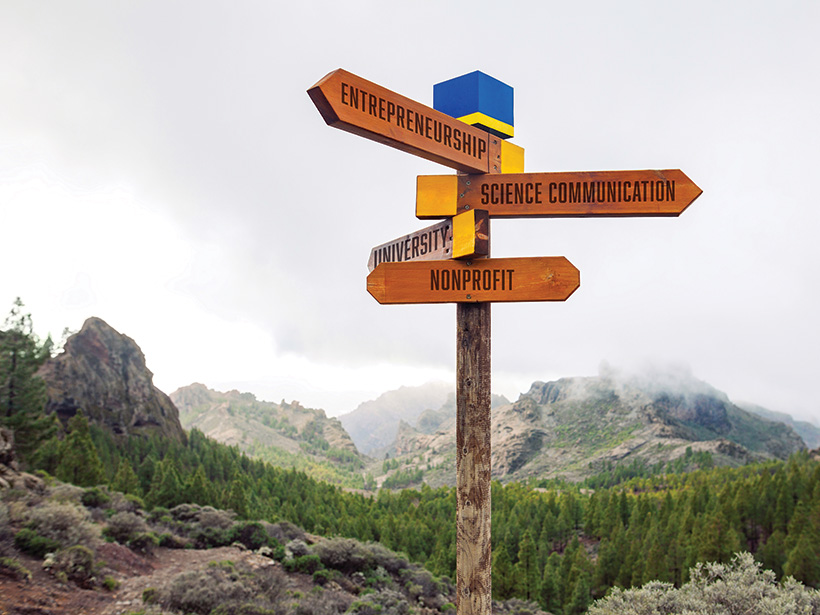 A signpost showing possible geoscience career pathways appears in the foreground of a photo of mountainous terrain.