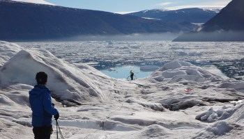 Two scientists stand atop a glacier holding cords and ropes, with a view of a fjord, icebergs, and mountains in the distance