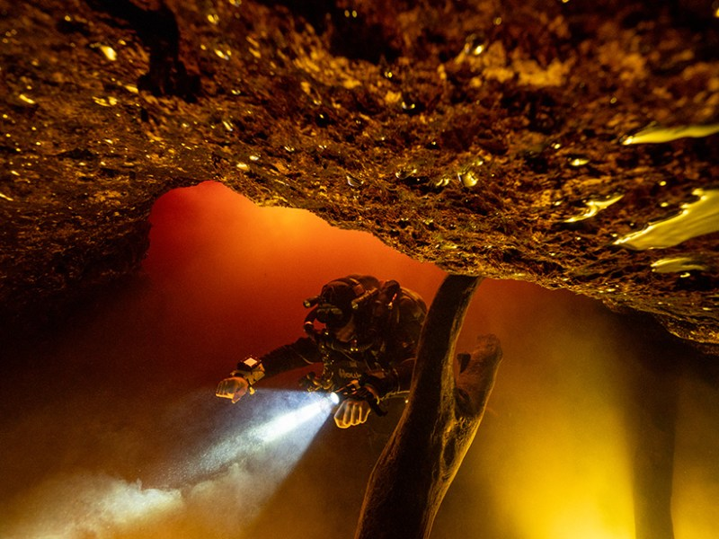 A scuba diver swims and shines a flashlight through brownish river water in a cave.