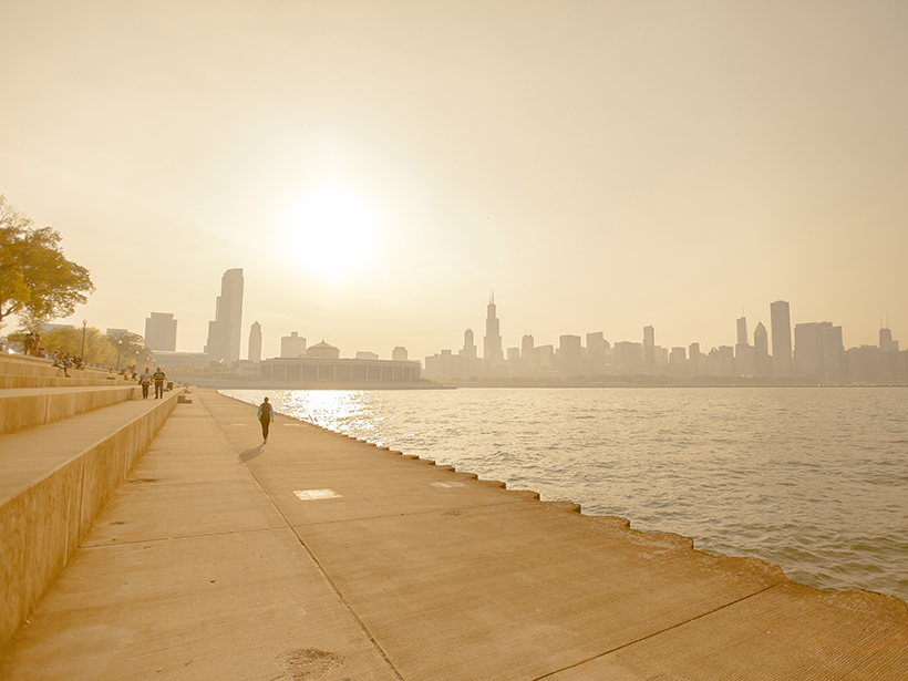 A yellow- and orange-tinted image of the Chicago skyline as seen from the shore of Lake Michigan. The summer Sun is high in the sky, and people walk and sit on a concrete path along the shore.