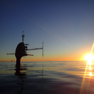 The tower of a research platform rises out of the ocean while the Sun sets on the horizon.