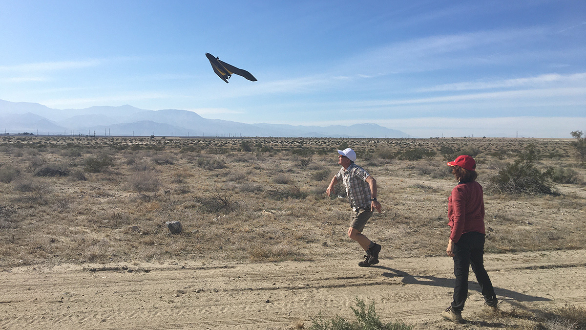 Against a blue sky streaked with white clouds, Michael Bunds runs along a dirt road as he lands a black fixed-wing drone. Chelsea Scott, wearing red, stands with her back to the photographer, watching the drone and looking at desert scrub in the foreground.