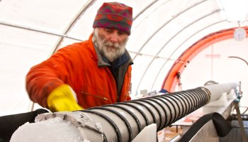 Image of a bearded and gloved man, Robert Mulvaney, with ice inside a metal corer.