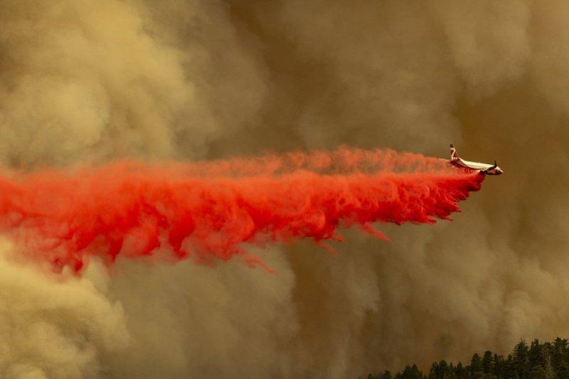 Um avião Coulson 737 adaptado para o combate a incêndios despeja um composto químico para retardar as chamas. Estima-se que o grau de contenção do fogo esteja em apenas 6%.