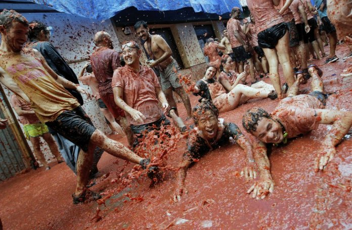 Varias personas se divierten durante la fiesta celebrada en la localidad de Buñol.