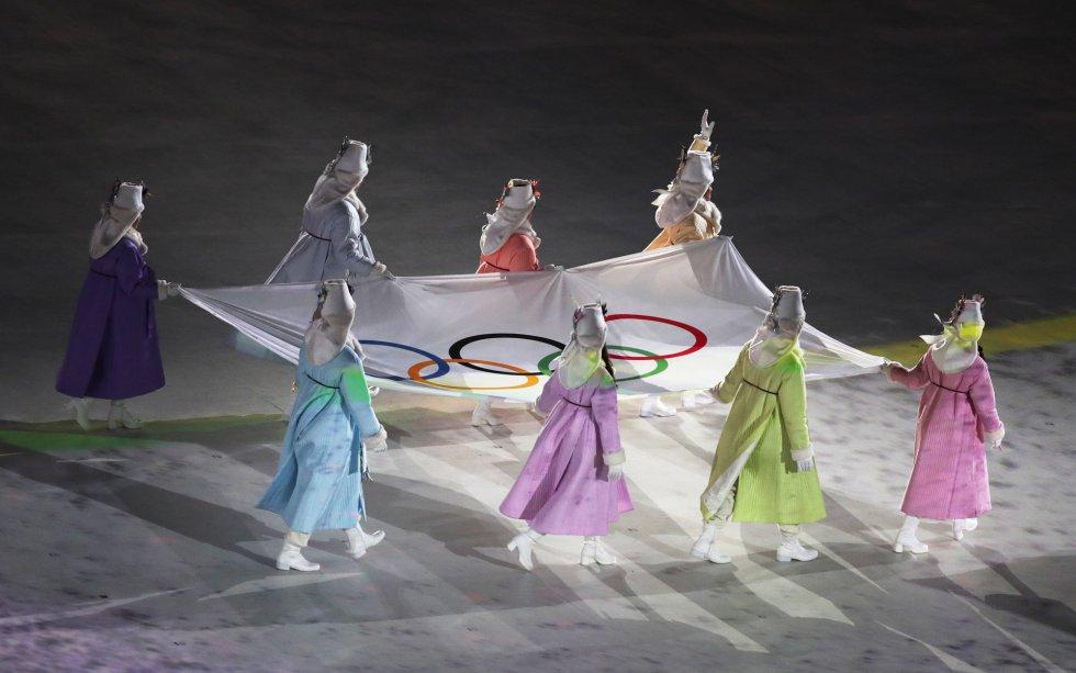 Voluntarias portan la bandera olímpica en el estadio de Pyeongchang durante la ceremonia de inauguración de los Juegos Olímpicos de Invierno 2018, el 9 de febrero de 2018.