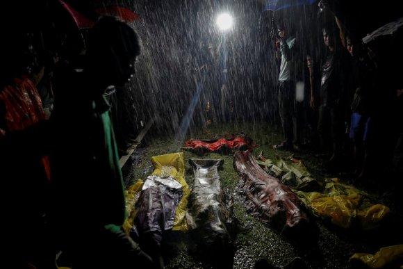 Pessoas se reúnem na chuva em torno dos corpos de alguns refugiados rohingyas que se afogaram na praia de Inani, perto do Cox's Bazar (Bangladesh), em 28 de setembro de 2017.