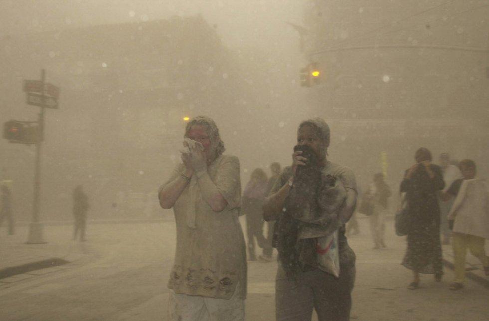 Varios ciudadanos aparecen cubiertos de polvo mientras huyen de la zona tras el desplome de las Torres Gemelas.