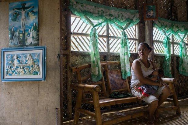 Una mujer de pescador da el pecho a su hijo. Los ingresos de las familias se ven afectados por la disminución de la población de peces.rn
