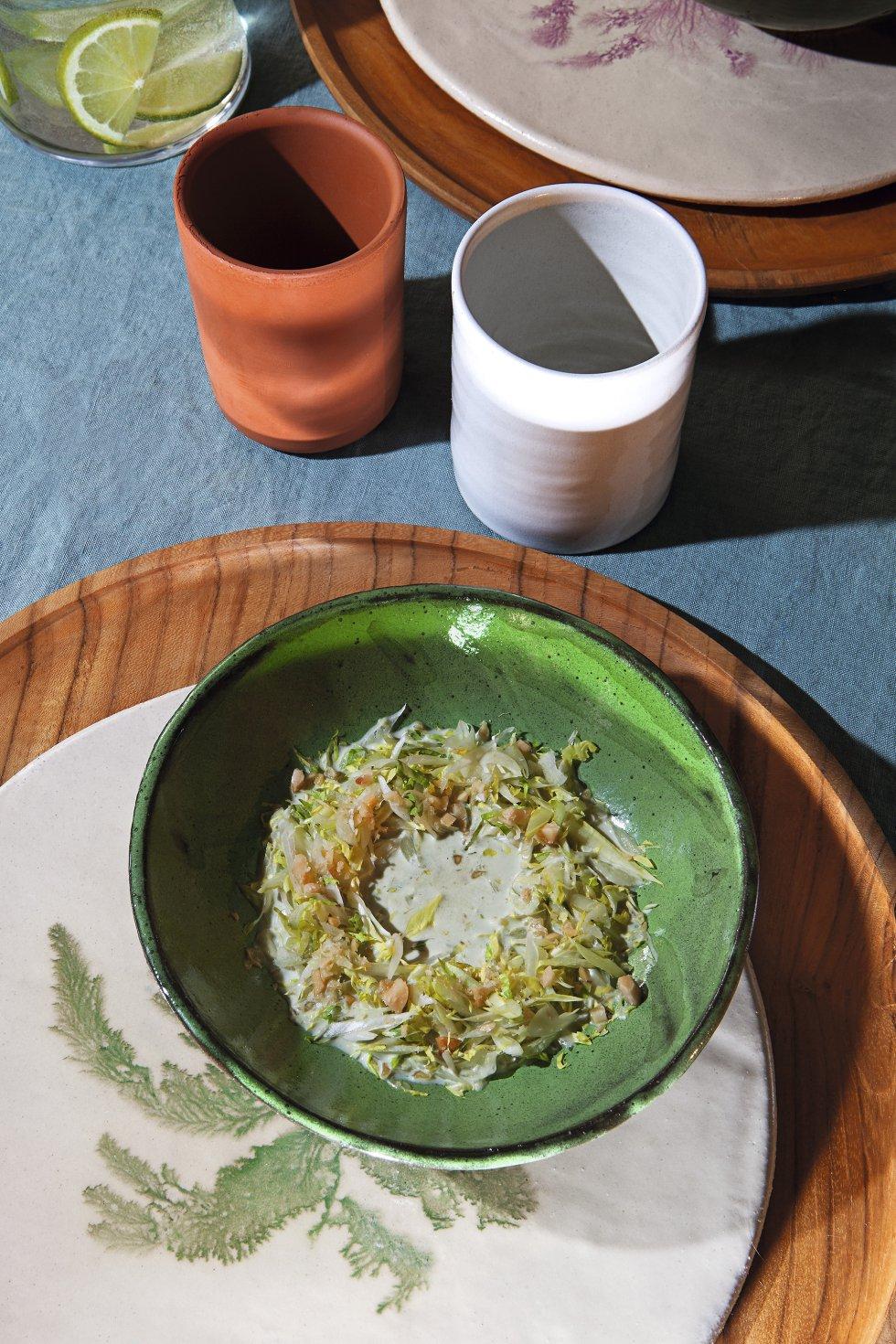 ACHICORIA CON CASTAÑAS Y AJOBLANCO DE PLANCTON     Ingredientes.  Para cuatro personas: 500 gramos de achicoria, 200 gramos de castañas peladas, asadas y troceadas. Para la sopa de almendras con plancton: 1 litro de leche de almendras, 450 gramos de almendra marcona frita, 2 dientes de ajo, 5 gramos de plancton, 25 gramos de agua, 15 gramos de vinagre de arroz blanco japonés, 10 gramos de jang (esencia de soja), 30 gramos de miga de pan blanco.    Elaboración.   1. En un bol introducir las almendras y la leche, añadir el ajo y la miga de pan. Dejar reposar esta mezcla durante al menos cinco horas. 2. Mientras se macera la mezcla, rehidratar el plancton en el agua. 3. Una vez tengamos ambas elaboraciones, triturar por un lado la mezcla de leche, ajos, almendras y miga de pan en un robot de cocina a máxima velocidad durante cuatro minutos. 4.Transcurrido el tiempo, pasar por un chino fino sin apretar demasiado para evitar que caigan posos de la almendra. 5. Añadir al ajoblanco el plancton rehidratado, el vinagre de arroz blanco y el jang. Reservar hasta su utilización en un recipiente de plástico hermético. 6. Limpiar bien la achicoria para despojarla de los restos de tierra que pueda tener. Quitar las capas exteriores y desecharlas, ya que son demasiado amargas. 7. Cortar el tallo de la achicoria en cubos de medio centímetro y la parte de las hojas en juliana muy fina. Reservar en agua y hielo. 8. Escurrir del agua y colocar en un plato en forma de corona. Espolvorear por encima las castañas. 9. Verter el ajoblanco en el centro de la corona en el último momento.   Los bajoplatos, de Mahe Homeware, son de madera de teca con certificado FSC (35 euros la unidad). El mantel, también de Mahe Homeware, es de lino 100% lavado a la piedra (70 euros). El plato y el cuenco de gres han sido diseñados por la ceramista María Gómez de Agüero (25 euros y 12 euros la unidad). Los vasos de gres blanco son de Laon Pottery (25 euros la unidad), y los de cerámica sin esmaltar, de Alfare