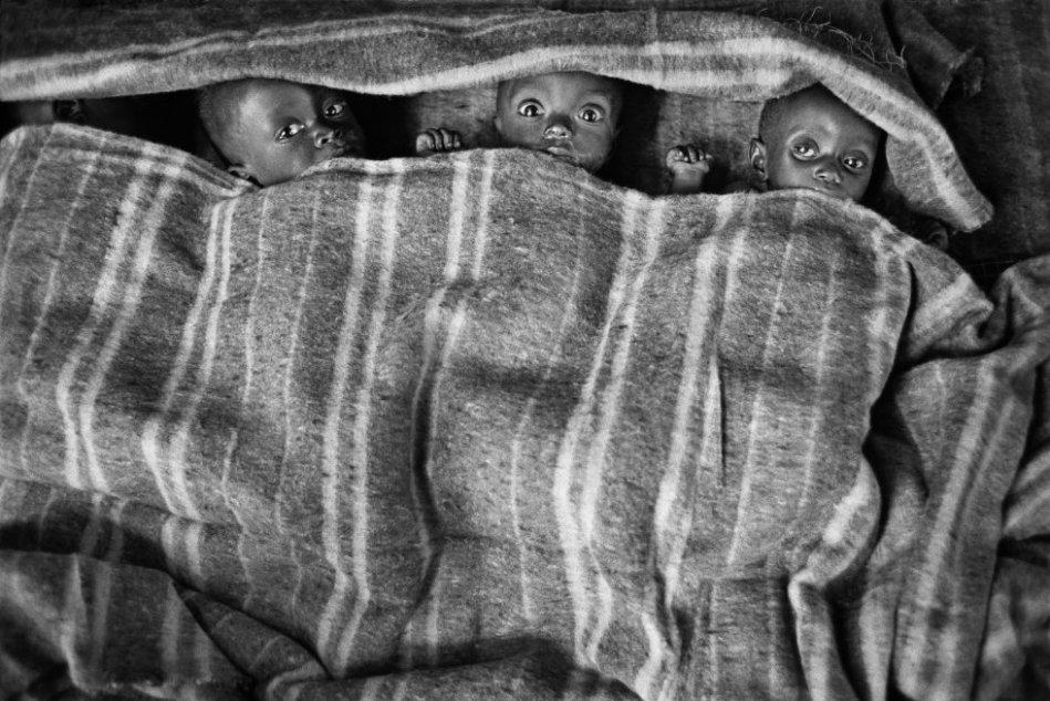 Tres niños acogidos en el orfanato junto al hospital que había en el campamento número uno de Kibumba. Goma, Zaire. 1994.
