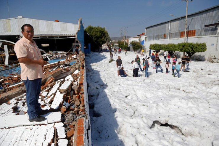 Los bomberos de Guadalajara y personal de Protección Civil de Jalisco trabajan en limpiar las toneladas de granizo y en la evaluación de los daños. En la imagen, un hombre junto a los escombros de un muro caído durante la tormenta.