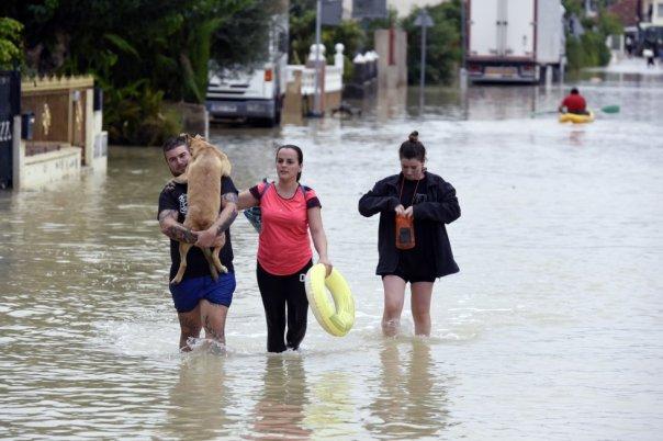Varios vecinos caminan por una calle inundada de El Raal (Murcia), este sábado, tras las fuertes lluvias.