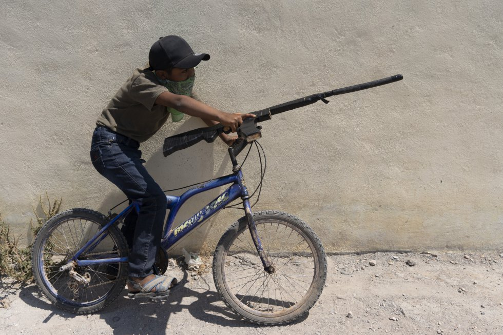 Un niño juega con su arma de madera montado en una bicicleta al término de la marcha.